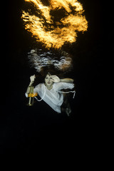 White dressed woman dives with a latern underwater