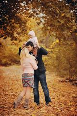 молодые родители  играют со своей маленькой дочерью в осеннем лесу