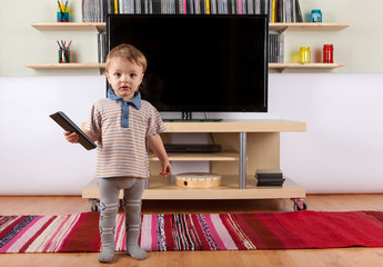 Cute baby boy with remote control in front of the TV