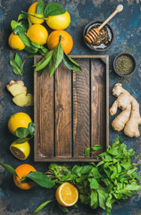 Ingredients for making natural hot drink with wooden tray in center. Oranges, mint, lemons, ginger, honey, apple over plywood background, top view, copy space. Clean eating, detox, dieting concept