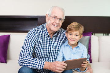 Happy senior man looking at photo with grandson
