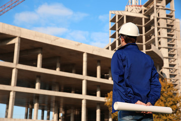 Handsome engineer with drawings standing against unfinished building