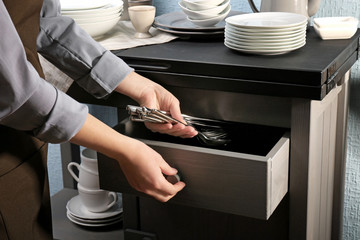 Woman putting silverware into drawer, closeup