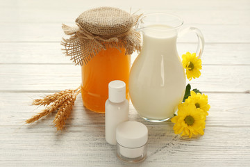 Honey, milk and cosmetics on wooden background