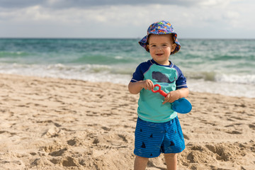 Happy little boy on the beach playing with a toy shovel