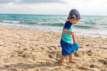 Happy little boy on the beach playing in the sand with a toy shovel
