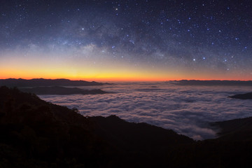 Milky way galaxy over foggy mountains in Thailand. Long exposure photograph.with grain