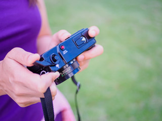 Pretty woman hand holding retro film camera with green grass field background