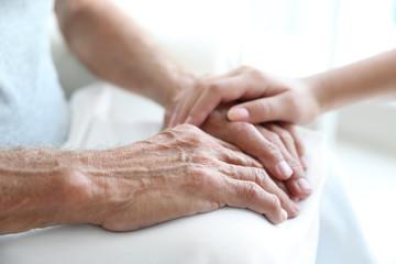 Young woman touching senior man hands, closeup