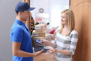 Young woman paying for package from courier