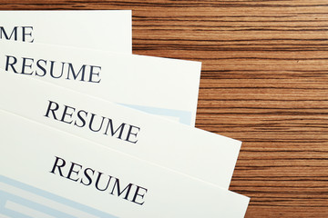 Resumes on wooden table, closeup