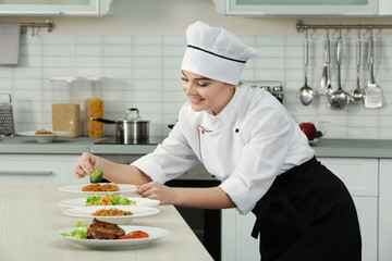 Young woman chef with different dishes on plates in modern kitchen
