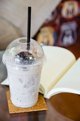 milk chocolate smoothie with open book on glass table