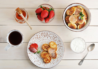 fritters with sour cream and strawberries, tea mug, honey with a stick of honey