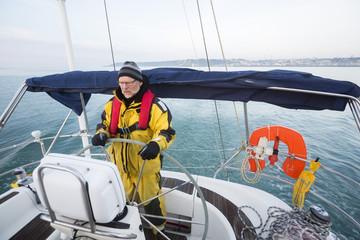 Man Wearing Waterproof Jacket While Steering Yacht In Sea