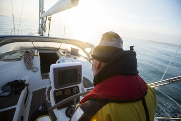 Man Looking At Navigational Screen On Sail Boat