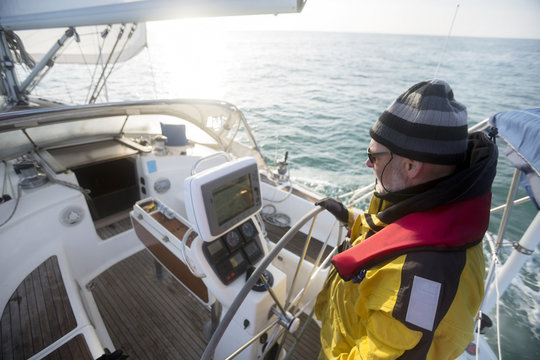Mature Man Steering Wheel Of Yacht In Sea