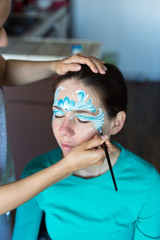 Woman painting face for girl, young woman. Work at home. Face painting. hobby