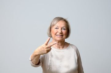 Senior woman showing V signs
