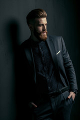 Stylish handsome bearded man in trendy suit standing with hands in pockets on black