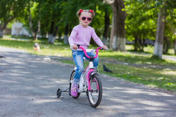 cute little girl in sunglasses with two tails katatsya in the city on a bicycle summer sunny day