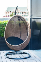 Wicker hanging chair swing with black pillow on wooden floor.
