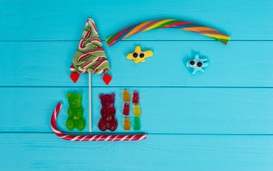 Cheerful picture of tasty jelly candies in the shape of bears sledging and trees