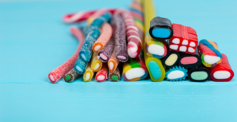 Colorful delicious licorice and chewy candies on wooden board