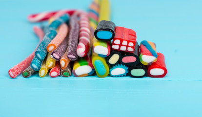 Colorful tasty licorice and chewy candies on wooden board