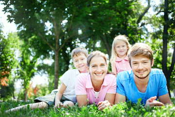 young happy family at noon in the park on the grass. Two young parents and children, boy and girl, lies on the grass and smiling looking at the camera.