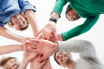 Low angle portrait of a group of students putting their hands in a huddle
