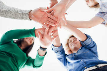 Group of positive-looking young  colleagues in a hands in huddle