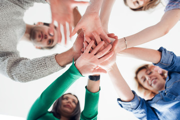 Group of co-workers standing in a circle with their hands in a huddle