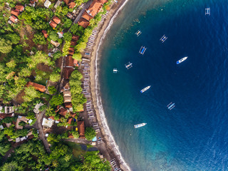 Aerial shot of calm lagoon with traditional boats and buildings on the shore. Bali, Indonesia