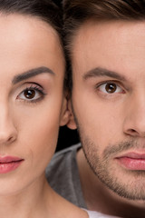 headshot of serious woman and man looking to camera on black