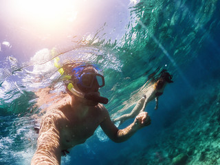 Young couple swimming under water in crystal ocean water at amazing island. Taking selfie.