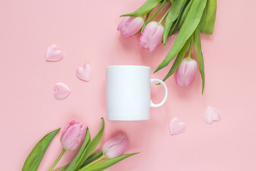 White coffee mug with pink tulips and hearts ona pink background. Space for text or design.