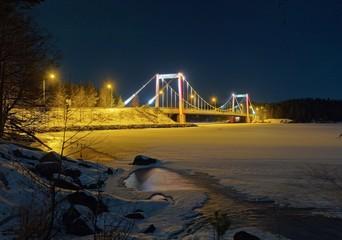 Suspension bridge and frozen lake in winter scene in Finland.