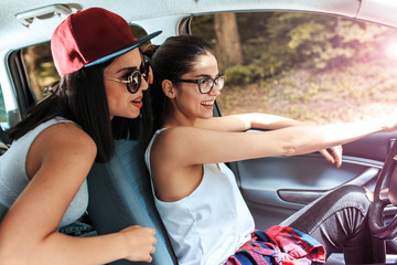 Two young female on car trip.They are driving the car and making fun.Positive emotions.