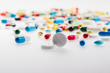 Close-up view of colorful medical pills on white, medicine and healthcare concept