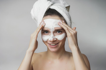 woman gets white mask on the face,applying scrub