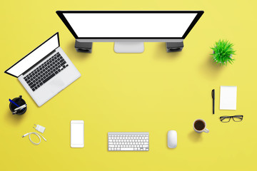 Yellow office desk with computer display, laptop, and mobile phone. Creative scene with free space for text.