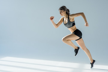 side view of running woman in sportive clothing on grey Wall mural