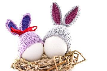 Easter eggs in the nest. Knitted Easter Bunny. Egg in Easter bunny cap.