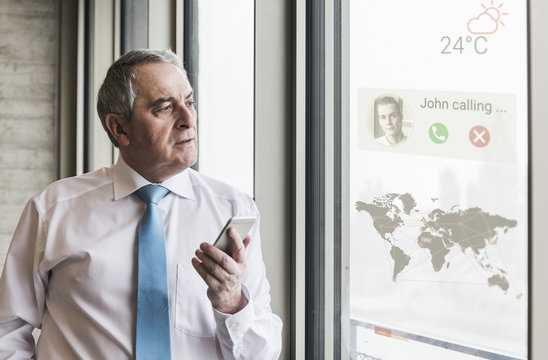 Businessman receiving a call on windowpane with world map in office