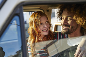 Smiling young woman looking at boyfriend in a car