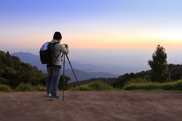 photographer takes photo of landscape and mountain