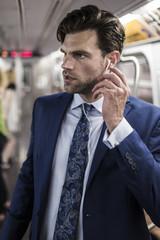 Businessman in metro using smart phone