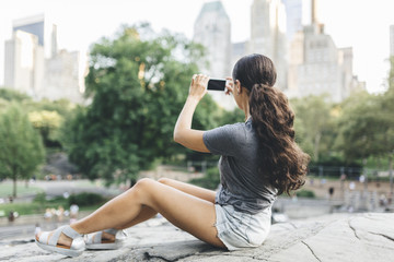 USA, Manhattan, young woman sitting in Central Park taking picture  of skyline with smartphone