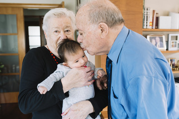 Great-grandparents with baby at home